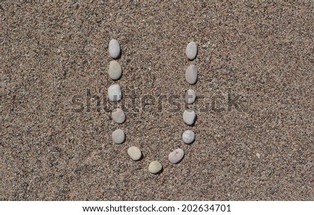 U letter made of stones on sand  - stock photo