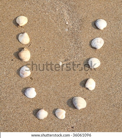 u letter symbol created from shells on a beach sand