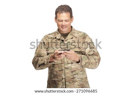 U.S. Army Soldier, Sergeant. Isolated and smiling at cell phone while sending a text message. - stock photo