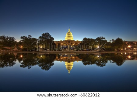 U.S. Capitol at night mirroring in the water - stock photo