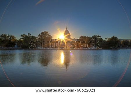 U.S. Capitol at sunrise mirroring in the water - stock photo
