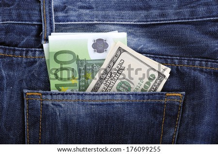 U.S. dollars and EURO in the back jeans pocket - stock photo