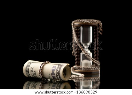 U.S.Dollars chained with hourglass with silver chain. Black background. Studio shot. - stock photo