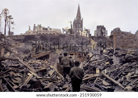 U.S. infantry patrol picking its way through the blasted ruins of Saint Lo. The town was 95% destroyed before it was captured from Germans on July 18, 1944. B&W Photo with oil color. - stock photo