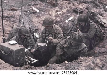U.S. soldiers of a shore fire control group operating Signal Corps radios. One man cranks the hand generator, while another uses a hand-held radio set. June 6-8, 1944, Normandy, France. - stock photo