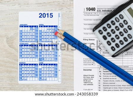 U.S. Tax form 1040 with calculator, calendar and pencils on wooden desktop  - stock photo