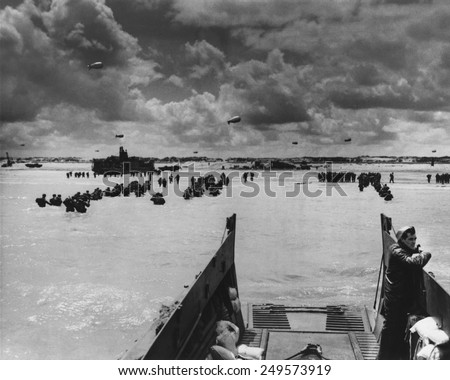 U.S. Troops land at Normandy on D-Day. With the beach taken and barrage balloons deterring German aircraft, soldiers and supplies flooded into France in June 1944, during World War 2. - stock photo