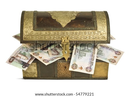 UAE Dirham bills popping out from an old wooden trunk. - stock photo