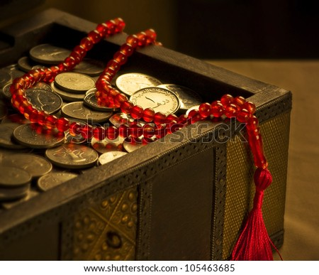 UAE Dirham coins in a trunk and a rosary - stock photo