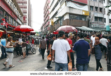 UALA LUMPUR, MALAYSIA - AUGUST 30: Shoppers in the crowded street bazaar on August 30, 2011 in Chinatown, Kuala Lumpur, Malaysia. The district is earmarked for demolition by 2012 for a new train line. - stock photo