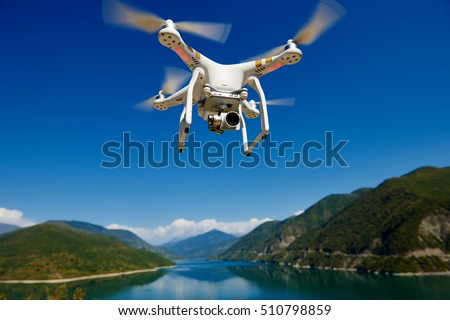 uav drone with high resolution digital camera flying in the blue sky over the mountain at lake