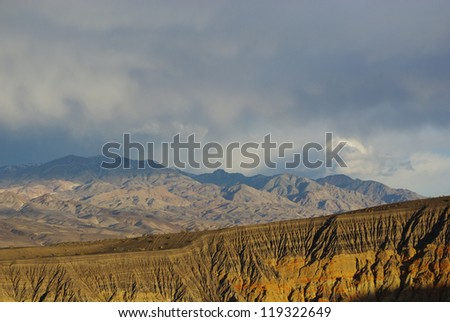 Ubehebe Crater and mountains under threatening skies, Death Valley, California - stock photo