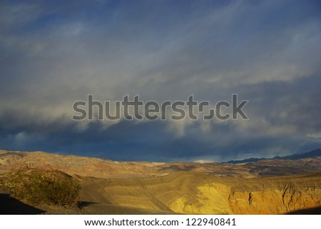 Ubehebe Crater rim and high mountains under threatening skies - stock photo