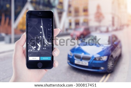 Uber application startup page on the Apple iPhone 5s display in female hand. Blurred street view with car and flare sun light on the background. Varna, Bulgaria - May 25, 2015. - stock photo