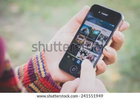 UBON RATCHATHANI, THAILAND - JANUARY 1, 2015: Hand holding Iphone and using Instagram application, Instagram is a popular online social networking service. - stock photo