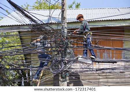Ubon Ratchathani, Thailand - January 20, 2014: Two Thai electricians are fixing confusing electricity lines on a pole. - stock photo