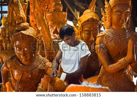 UBON RATCHATHANI, Thailand - July 11, 2013: A craftsman of Wat Phasukaram temple was crafting candle figures.