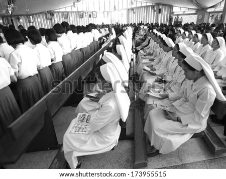 UBON RATCHATHANI, THAILAND - MAR 19, 2012 :  Row of nuns sitting calmly in church for Catholic funeral of priest Luca Santi Wancha on Mar 19, 2012 in Ubon Ratchathani, Thailand