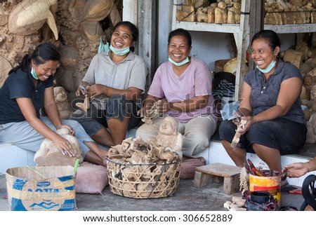 UBUD, BALI, INDONESIA - MARCH 23, 2015 : Unidentified women are making wooden souvenirs for tourists. Woodcarving is a traditional handicraft in Bali - stock photo