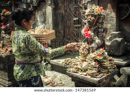 UBUD, INDONESIA-Aug 29: unidentified woman praying god in Ubud, Bali, Indonesia, on 29 aug 2009. Every morning women bring flowers and incense to their gods - stock photo