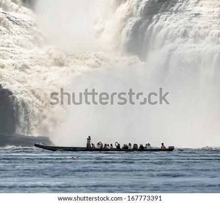 Ucaima waterfall and tourists boat in the lagoon of Canaima national park - Venezuela, Latin America - stock photo