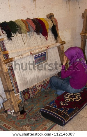 UCHISAR, TURKEY - SEPTEMBER 1, 2012: Islamic woman making a rug at Gallery Cappadocia on September 1, 2012.  Gallery Cappadocia is preparing to enter another International Carpet Competition.