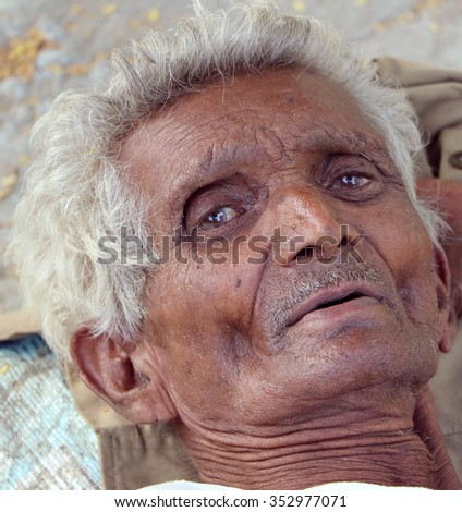 Udaipur, India - September 12, 2015: An unidentified sad old man was lying down helpless in the zoo in Udaipur, Rajasthan, India.