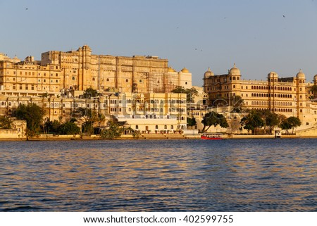 UDAIPUR, INDIA - 20TH MARCH 2016: A view towards the City Palace from Pichola Lake in Udaipur during the day. Tour boats and people can be seen. - stock photo