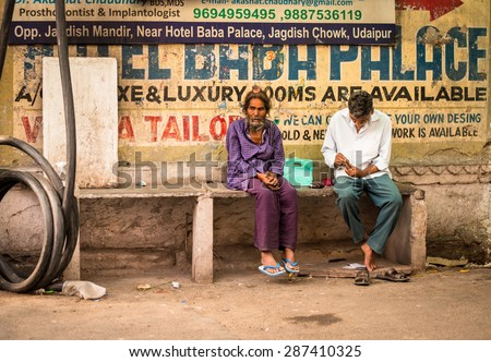 UDAIPUR, RAJASTAN / INDIA - MAY 28 2013 - Two Unidentified men outside a fabric. - stock photo