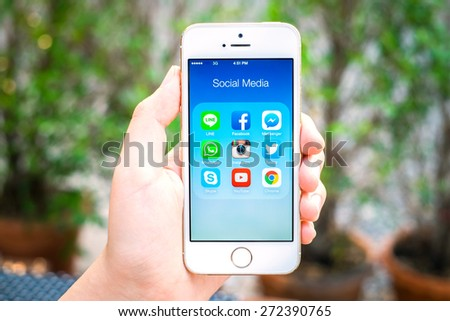 UDON THANI, THAILAND - April 25, 2015: All of popular social media icons on smartphone device screen with hand holding on Apple iPhone 5s. - stock photo