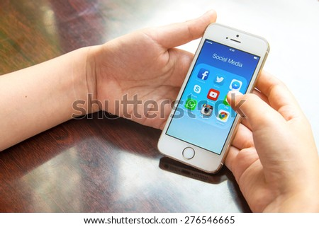 UDON THANI, THAILAND - April 21, 2015: All of popular social media icons on smartphone device screen with hand holding on Apple iPhone 5s. - stock photo