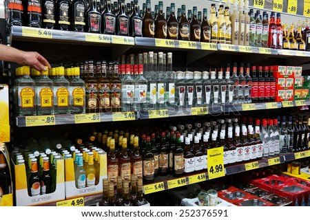 UELSEN, GERMANY - SEPTEMBER 22: Hand takes a bottle from aisle filled with spirits in a Lidl supermarket, their concept is selling mainly house brands, taken on September 22, 2014 in Uelsen, Germany - stock photo