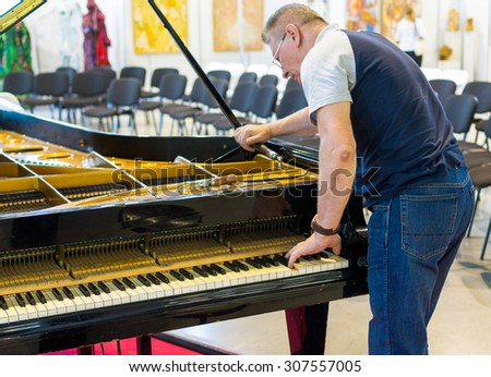 UFA/BASHKORTOSTAN - RUSSIA 11TH AUGUST 2015 - Professional piano tuner works on a grand piano before a musical performance in Ufa Russia in 2015
