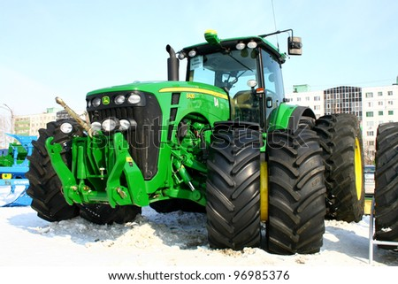 """UFA, RUSSIA - MARCH 14: Large modern John Deere 8430 four wheel drive tractor with double wheels exhibited at the annual motor show """"Agrocomplex"""" on March 14, 2011 in Ufa, Russia. - stock photo"""