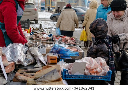 UFA - RUSSIA 12TH NOVEMBER 2015 - Young Russian by looks at fresh fish on display at a local fishmonger stall in Ufa, Russia during November of 2015. The fish are a valuable food resource for winter - stock photo