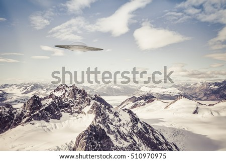 UFO flying over Alaska mountain wilderness with clouds.