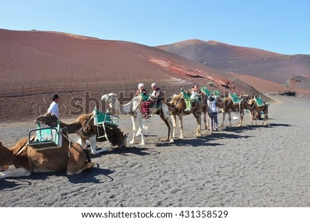 UGA, LANZAROTE, SPAIN  March 15, 2016: Some tourists on the back of camels are starting a trip through the desert. In Timanfaya National Park, Lanzarote, Canary Islands, Spain. - stock photo