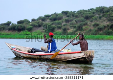 UGANDA - AUG 29, 2010: Two fishermen in a boat moving on the Nile at twilight. The Nile river is the only source of transportation in this region of central Africa - stock photo