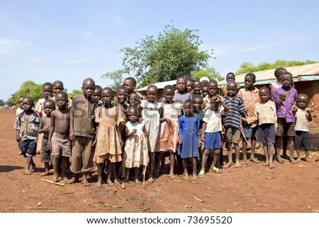 UGANDA - AUGUST 9: Children of the Karamojong ethnic look with curiosity, the Karamojong are in the process of disarmament, August 9, 2010 in Karamoja, Uganda - stock photo