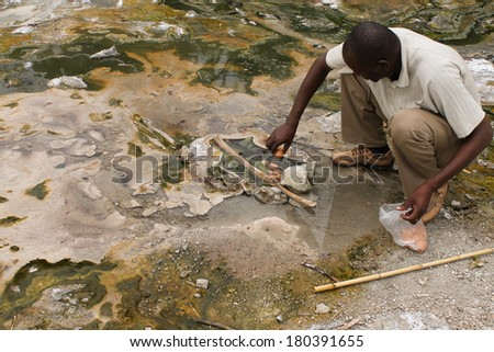 Uganda - 6 March: African man cooks eggs and bananas in the hot springs Semuliki National Park 6 March 2012 in Uganda