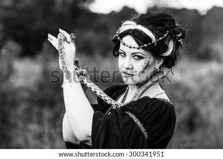 Ugly woman with snake. Witch conjure outdoors - stock photo