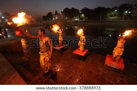 UJJAIN - INDIA - JANUARY 4, 2016: Unidentified Hindu priests performing a religious aarti on January 4, 2016 in Ujjain, India. Ujjain will host the world-famous Hindu pilgrimage Kumbh Mela in Mai 2016 - stock photo