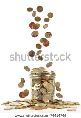 uk currency falling into a savings jar - stock photo