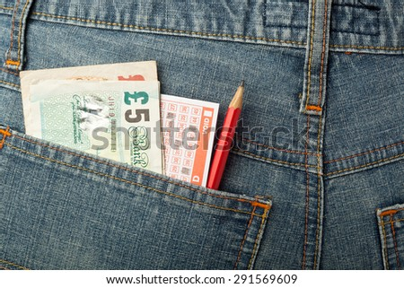 UK money and lottery betting slip in back pocket