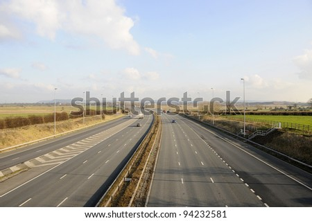Uk motorway with traffic driving in both directions during the day time. Showing various trucks and cars passing by