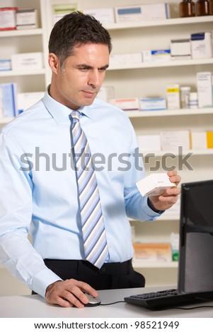 UK pharmacist working on computer - stock photo
