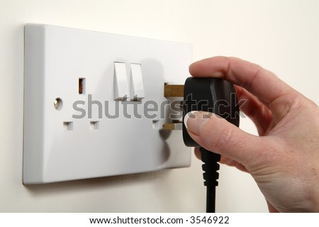 UK plug about to be plugged into a white wall socket