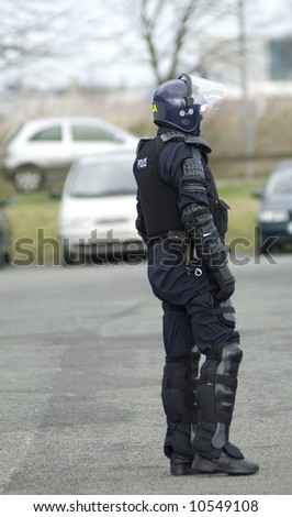 Uk police officer in full riot gear at the scene of a public disturbance.