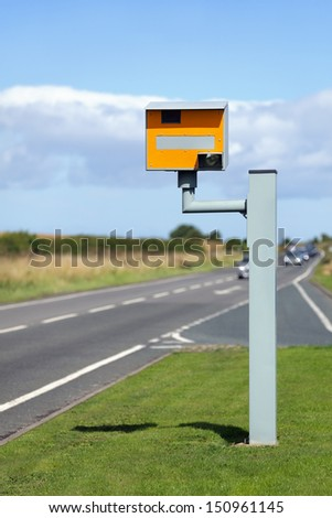 UK static speed camera with speeding cars approaching on a rural road - stock photo