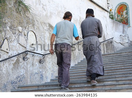 Ukraine, Bakhchisaray - September 06, 2011: Monks of the Holy Dormition Monastery going up the stairs to the temple - stock photo